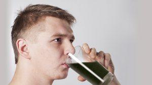 Homem tomando copo de água com carvão ativado
